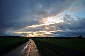 Wet reflecting country road made of concrete slabs is leading through the dark fields under a dramatic cloudy sky with evening sun, rural landscape near Schaalsee in Mecklenburg-Western Pomerania, northern Germany, copy space