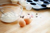 baking cupcakes with eggs, flour and muffin tin on a wooden kitchen board, copy space