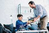 Joyful father and his son holding a robotic device