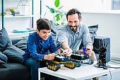 Cheerful father and his son constructing robotic devices