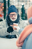 Senior man in winter clothes drinking coffee with friend