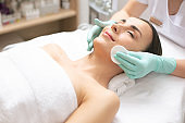 Smiling woman relaxing while having her face cleaned