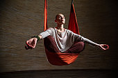 Beautiful woman relaxing while meditating during aerial yoga