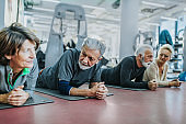 Group of active seniors resting on a break in a gym.