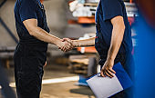 Unrecognizable manual workers came to an agreement in a factory.