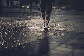 Unrecognizable male person running on a rain.