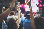 Back view of crowd with raised arms on a music festival.