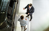 Above view of car salesperson talking to his customer in a showroom.