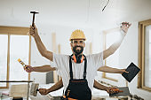 Happy multi-tasking construction worker in renovating apartment.