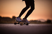 Unrecognizable person skateboarding at sunset.