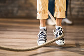 Unrecognizable person skipping a rope on the floor.