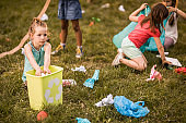 Group of kids cleaning the park from garbage together.
