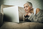 Smiling mature woman using laptop while relaxing in the living room.