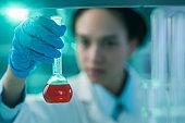 Close up of biochemist examining liquid in a beaker.