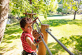 Little boy walking on the rope at adventure park