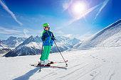Boy stand on fresh ski slope over mountain peaks