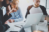 Business meeting concept.Coworkers team working with mobile computer at modern office.Analyze business plans,using laptop.Blurred background.Horizontal.