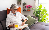 Pretty senior lady relaxing on the sofa reading a book and drinking a fruit juice. Gray hair and eyeglasses. Bright light from window. Plants and flowers on background