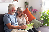 Two elderly people sitting together on the sofa looking in internet a beautiful place for vacation