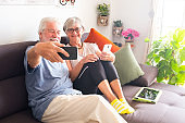 Two senior people take a selfie smiling and relaxing on the sofa. Bright light from window. Technology and wireless