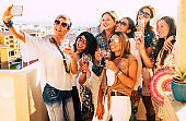Group of people women enjoying aperitif on the terrace celebrating a birthday and a future wedding. Take a selfie for absent friends with large smiles