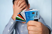 Confused man looking at many credit cards uncertain which one to choose on blue background. young man is holding a stop of credit and debit cards in a pensive pose. The guy chooses a card to pay