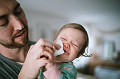 Father Holding Infant Sick With Cold Virus
