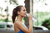 attractive sporty female with water bottle, outdoor exercising