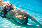 young woman diving in swimming pool, underwater shot