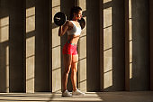 female bodybuilder with barbell on shoulders near concrete wall