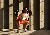 strong smiling female squatting with barbell near concrete wall