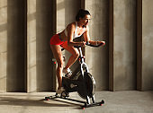 sporty female cardio training on exercise cycle in gym