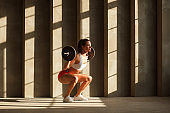 sportswoman squatting with barbell near concrete wall