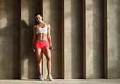 athletic attractive female posing with dumbbells near concrete wall