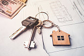 concept of real estate sale or lease. Keys with keychain and American dollars in the form of a house lying on a paper with a plan of the house. mortgage
