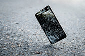 Accident with gadget concept. Device need repairing. Copy space. Mobile phone falling and crashes on asphalt, broken smartphone flying down to ground. Smashed, destroyed, damaged cellphone.