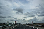Bulgarian highway with cars and truck, asphalt road with road signs on the side, foggy weather