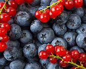 Texture berries close up. Top view. Black-blue and red berries. Ripe blueberries and red currants. Various fresh summer berries.