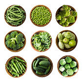 Vegetables isolated on a white. Squash, green peas, broccoli, kale leaves and green bean in wooden bowl. Vegetables with copy space for text. Top view. Studio photo. Fresh green vegetables isolated on a white background. Isolated macro food photo close up