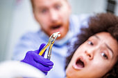 Dental nippers gripping an extracted tooth