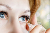 A closeup of a woman inserting a contact lens into her eye.