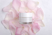Top view of closed glass jar full of moisturizing cream on the pink rose petals