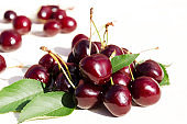Ripe cherries with green leaves, natural sunlight