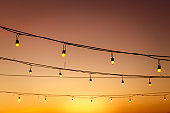 vintage light bulbs on string wire against sunset decor in outdoors wedding event party