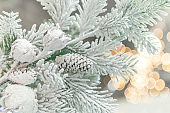 New Year and Christmas decor. Festive background with decorative artificial shining snow-covered branches of Christmas trees in green with pine cones