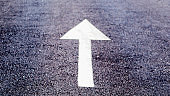 White arrow sign on asphalt road, Traffic symbol on street, Surface rough Texture Background