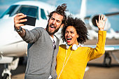 Rich afro-american girl waving while taking a selfie with her partner next to a private jet parked on an airport runway