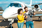 Vlogger couple creating content together next to the nose cone of a private jet parked on an airport runway