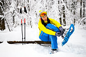 Hiker sitting on a small wooden bench covered with snow in a frozen forest, adjusting her snowshoe binders