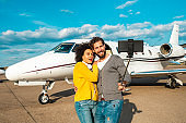 Famous young couple taking a selfie on a smart phone mounted on a selfie stick in front of a private airplane parked on an airport runway